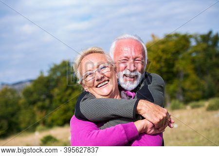 Elderly Couple Embracing In Autumn Park. Enjoying In Love.