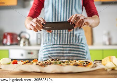 Female Chef Blogger Takes Photos Of Home-made Pizza On Her Phone. The Concept Of Food Photography Fo