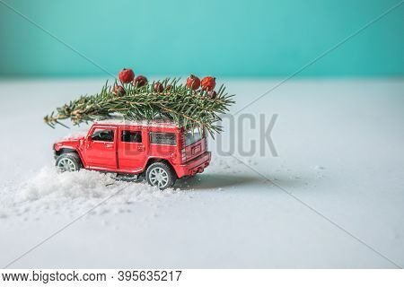 Miniature Red  Car Toy Delivering Christmas Fir Tree On Blue Background. Christmas Greeting Card Con