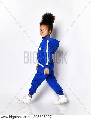 Happy Smiling Dark-skinned Afro-russian Kid Girl Sportsman Athlete In Blue Trendy Jumpsuit Walks Pas