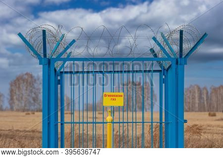 Shot Of A Caged Industrial Gas Station With Barbwire On Top Of The Fence. Yellow Gas Pipe In The Mid