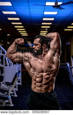 Strong Young Athlete With Beard Showing Sport Physique In Athletic Workout Gym