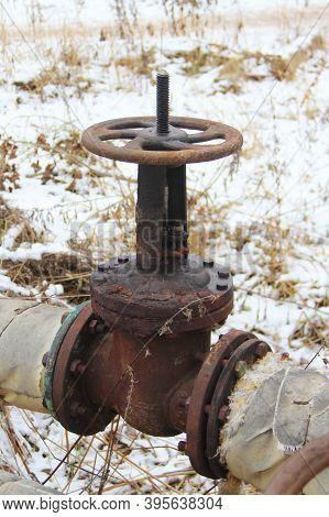 Old Damaged And Rusty Iron Oil Pipe Valve Wheel. Metal, Pipeline And Mechanic Concept. An Old Iron V