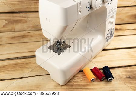 Electric Sewing Machine With Sewing Accessories, On A Wooden Background. White Sewing Machine And Mu