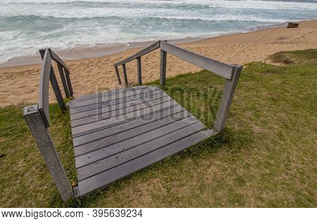 Wooden Stairs Leading From Grassed Area Onto Beach