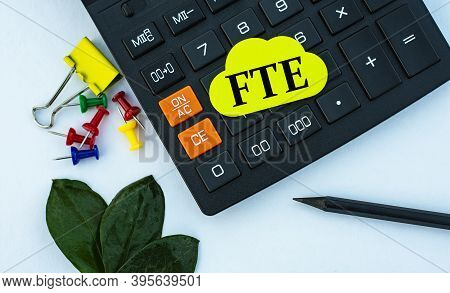 Fte (full-time Equivalent) - Word On Yellow Note Sheet On White Background With Calculator, Pencil,