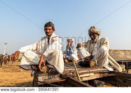 November 2019 Pushkar,rajasthan,india. A Group Of Three People Sitting On Wooden Cart At Pushkar Cam