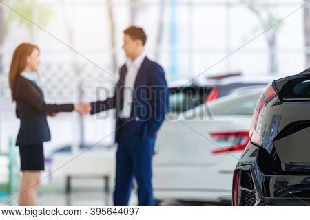 Selective Focus On A New Car And Blur The Dealership Professional Salesman And His Client Shaking Ha