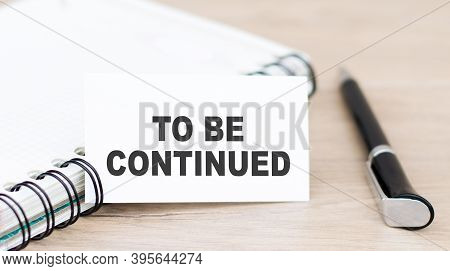 Text To Be Continued On A White Card, Which Is Next To The Notebook And Pen On The Table.