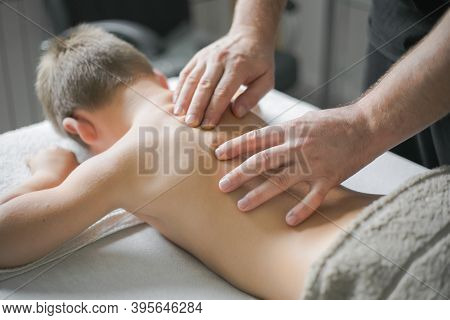 Professional  Physiotherapist Is Treating A Kid In Clinic. Boy Toddler Relaxes From A Therapeutic Ma