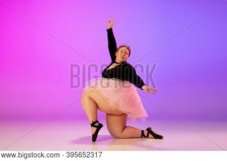 Prima. Beautiful Caucasian Plus Size Model Practicing Ballet Dance On Gradient Purple-pink Studio Ba