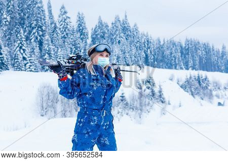 Portrait Of A Woman Skier In Medical Mask During Covid-19 Coronavirus On A Snowy Mountain At A Ski R