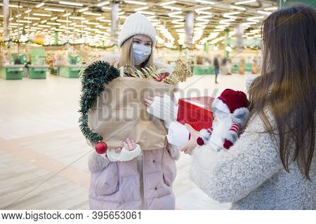 Young Women In Medical Mask Shopping For Christmas In Mall. Xmas Holidays In New Covid-19 Reality. S
