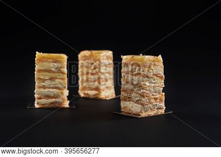 Three Square Pieces Of White And Yellow Creamy Cake, Sweet Delicious Dessert Isolated On Black Backg