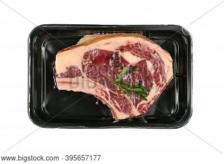 Close Up One Marbled Raw Ribeye Beef Steak With Rib Bone Vacuum Sealed With Black Plastic Film, Isol