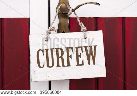 White Wooden Board Hanging On A Golden Door Handel With Message Curfew