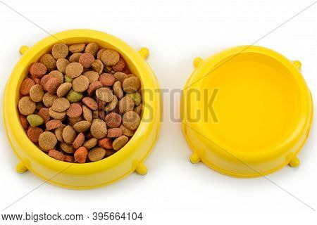 Yellow Bowls Of Crunchy Kibbles And Water On White Background