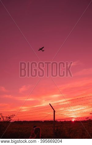 Orange Hanging Curtains Of Smoke From A Large Wildfire And Obscuring A Firefighting Plane In The Sky