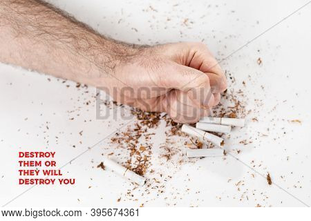 The Concept Of Nicotine Addiction And Anti-smoking. A Mans Fist Smashes The Cigarettes, And The Toba