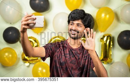 Young Man On Video Call Or Chat On Smartphone During 2021 New Year Or Christmas Celebration On Decor