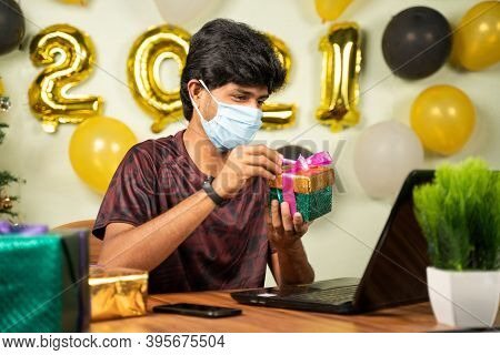 Young Man With Medical Mask Opening Gift Box Over Video Call On Laptop With 2021 New Year Decorated