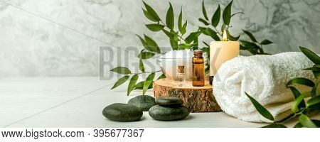 Beauty Treatment Items For Spa Procedures On White Wooden Table. Massage Stones, Essential Oils And