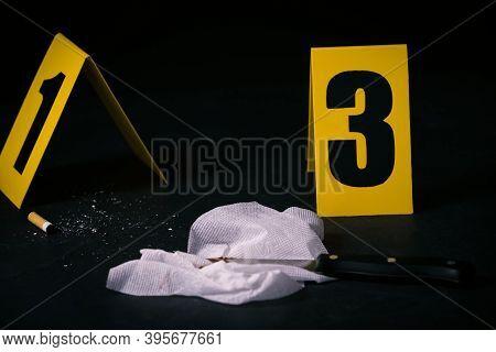 Stub, Knife And Bloody Napkin On Black Slate Table At Crime Scene
