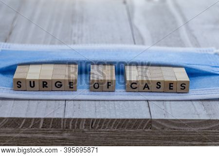 Surge Of Cases On Face Mask Covid Pandemic Alert Concept Wood Block Letters On Board Cool Blue Tone