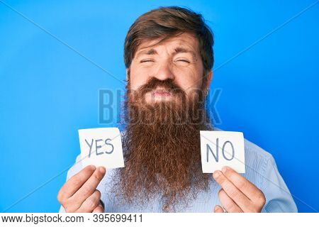 Handsome young red head man with long beard holding yes and no reminder puffing cheeks with funny face. mouth inflated with air, catching air.