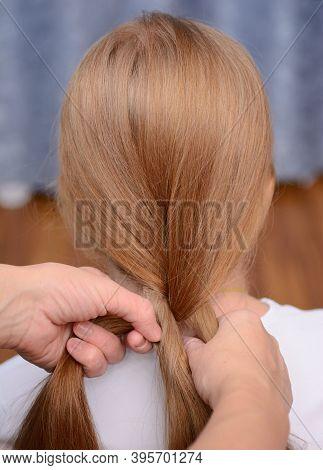 Women's Hands Do Their Hair, Braid Their Braids. Close Up