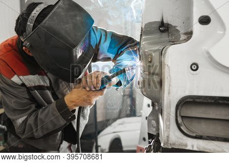 Worker Welds Car. Metalworking With Carbon Dioxide Welding.