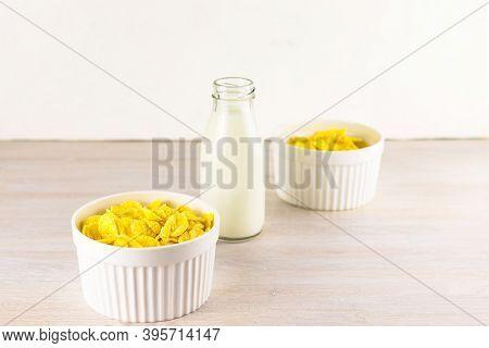 Corn Flakes In White Scandinavian Bowls Ramekin And Milk Bottle For Breakfast On White Wooden Table