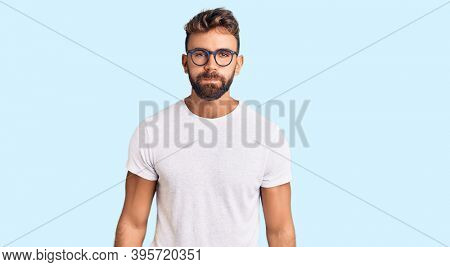 Young hispanic man wearing casual clothes and glasses puffing cheeks with funny face. mouth inflated with air, crazy expression.