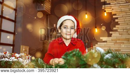 Emotional Cute Boy In Santa Claus Cap On Blurred Golden Background With Lights. Christmas Time, Atmo