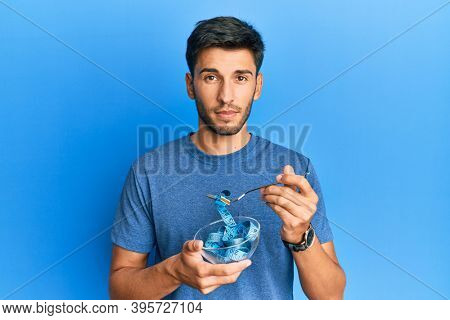 Young handsome man eating measure meter doing diet for weight loss relaxed with serious expression on face. simple and natural looking at the camera.
