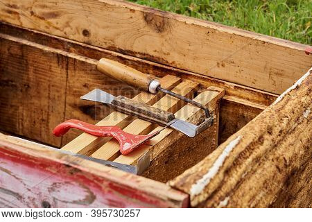 Beekeeper Tools Are Laid Out On Honeycomb Frames In An Opened Hive