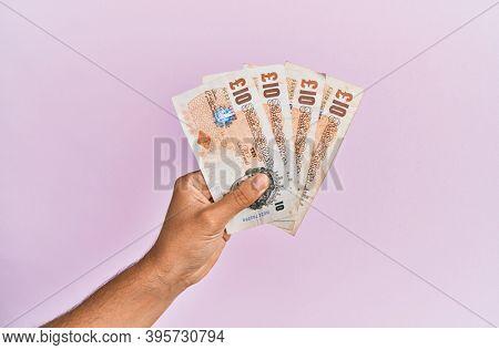 Hispanic hand holding 10 uk pounds banknotes over isolated pink background.