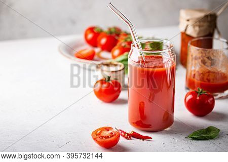 Glass Of Tomato Juice With Basil And Fresh Tomatoes On White Background