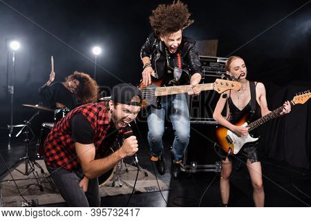 Kyiv, Ukraine - August 25, 2020: Vocalist Shouting In Microphone While Leaning Forward Near Guitaris