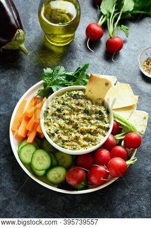 Baba Ganoush (roasted Eggplant Dip) In Bowl And Fresh Organic Vegetables Over Blue Stone Background.