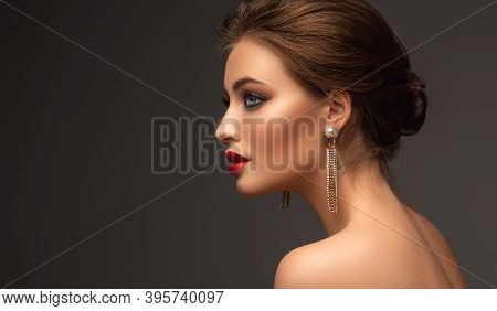 Beautiful Woman With Red Lipstick On Her Lips And Long Earrings. Beauty Girl With Elegant Hairstyle
