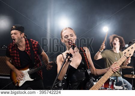 Kyiv, Ukraine - August 25, 2020: Blonde Vocalist With Electric Guitar Singing In Microphone Near Gui