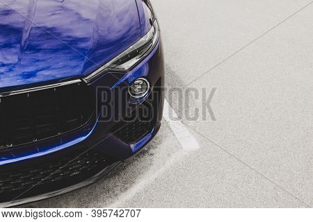 Part Of A Blue Car On A Background Of Asphalt. Car Headlights. Luxury Headlights