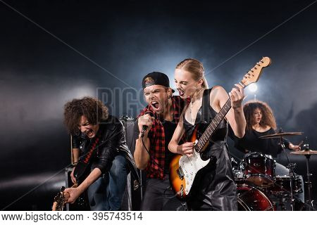 Kyiv, Ukraine - August 25, 2020: Vocalist Shouting In Microphone Standing Near Guitarists With Woman