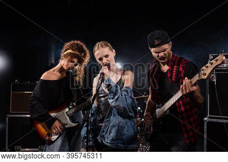 Kyiv, Ukraine - August 25, 2020: Blonde Vocalist Of Rock Band Singing Near Musicians With Bass Guita