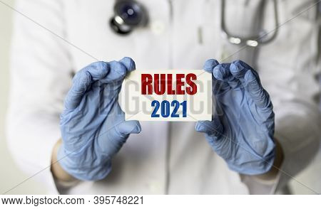 A Medical Worker In Gloves Holds A Card With The Words Rules 2021. Concept Of Rules In Medicine For