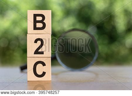 B2c Short For Business To Consumerabbreviation On Wooden Cubes On A Table With A Magnifying Glass Ov