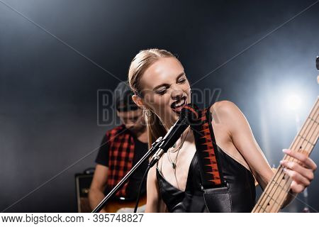 Kyiv, Ukraine - August 25, 2020: Rock Band Vocalist With Electric Guitar Singing In Microphone With