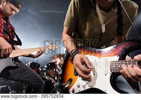 Kyiv, Ukraine - August 25, 2020: Rock Band Musician Leaning And Playing Electric Guitar With Pick Wi