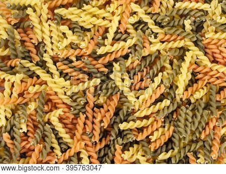 Dry Pasta Fusilli. Fusilli Have Spiral Shape And Yellow , Green, Orange  Color. Pasta Is Delicious I